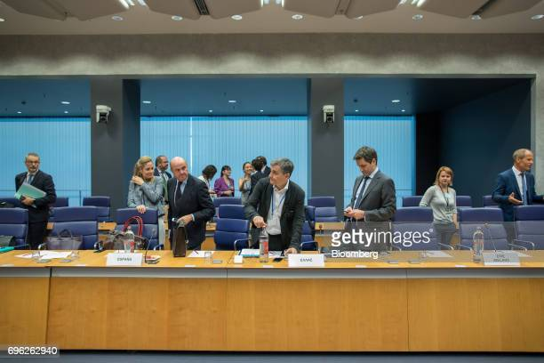 Euclid Tsakalotos Greece's finance minister center prepares to take his seat as Luis de Guindos Spain's finance minister center left looks on ahead...