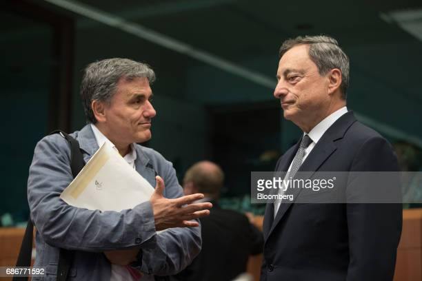 Euclid Tsakalotos Greece's finance minister left gestures as he speaks with Mario Draghi president of the European Central Bank ahead of a Eurogroup...