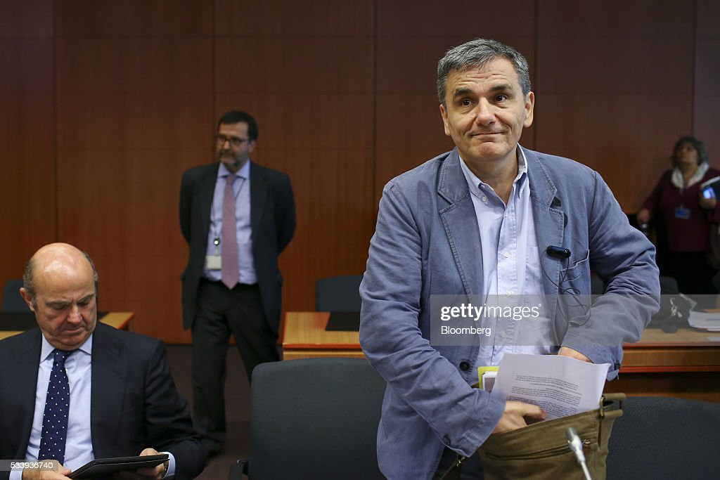 Euclid Tsakalotos, Greece's finance minister, right, arrives for a roundtable discussion as Luis de Guindos, Spain's economy minister, left, holds a tablet device during a Eurogroup meeting of European finance ministers in Brussels, Belgium, on Tuesday, May 24, 2016. Five years after handing Greece the biggest sovereign-debt write-off in history, European policy makers have come full circle to the point they had all hoped to avoid: a real discussion on debt relief. Photographer: Jasper Juinen/Bloomberg via Getty Images