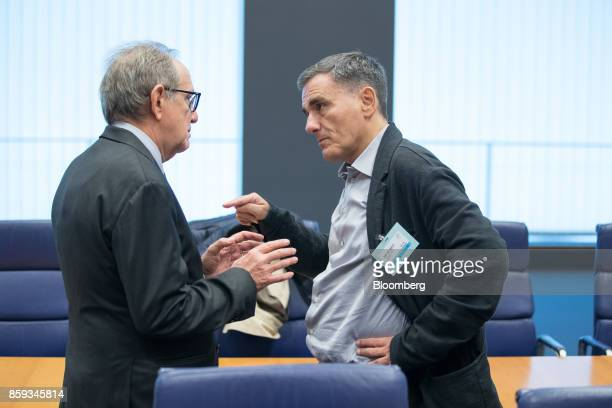 Euclid Tsakalotos Greece's finance minister right gestures while speaking with Klaus Regling managing director of the European Stability Mechanism...
