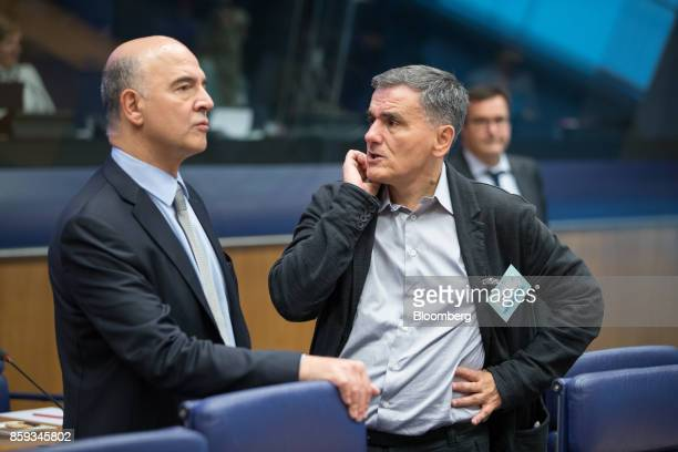 Euclid Tsakalotos Greece's finance minister right speaks with Pierre Moscovici economic commissioner for the European Union ahead of a Eurogroup...