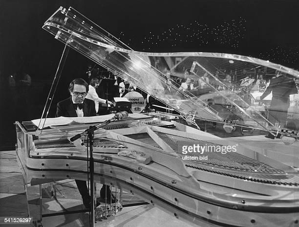 Eugen Cicero*1940Musiker Jazzmusiker PianistPorträt am Schimmel Konzertflügel im Hintergrund das RIAS Tanzorchester unter Horst Jankowski 1985