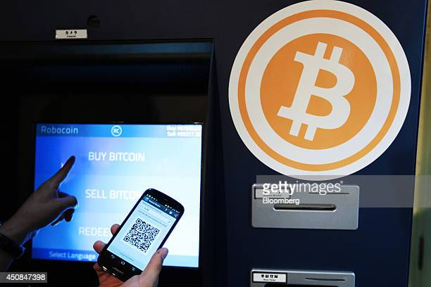 Eugene Aono a spokesperson for BMEX bitcoin exchange demonstrates usage of the company's Robocoinbranded automated teller machine at The Pink Cow...