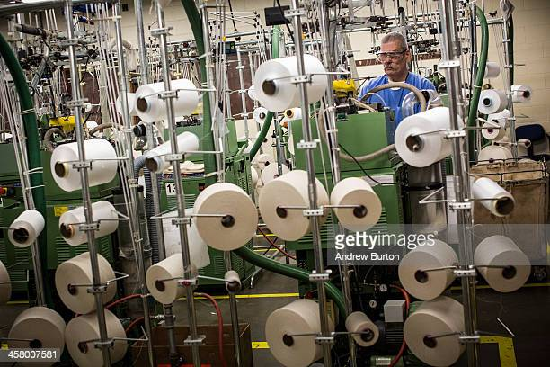 Eugene Bookout age 57 monitors a series of machines making socks in a prison factory at California Men's Colony prison on December 19 2013 in San...