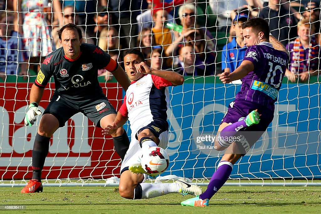 Eugene Galekovic and Marcelo Carrusca of Adelaide look to block a shot on goal by Jamie Maclaren of the Glory during the round 11 A-League match between Perth Glory and Adelaide United at nib Stadium on December 22, 2013 in Perth, Australia.