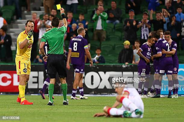Eugene Galekovic of Adelaide remonstrates with Referee Jarred Gillett while being issued a yellow card as Glory players celebrate a goal during the...
