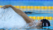 Eugene Godsoe of the USA competes in the Men's 100m Backstroke heats during the FINA Swimming World Cup at Hamdan Sports Complex on August 31 2014 in...