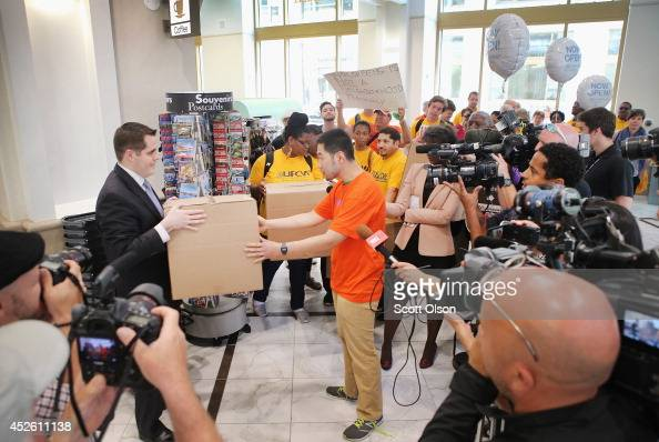 Eugene Lin presents to Walgreens store manager Steve Kukla a box which was reported to contain petitions with a portion of the 70000 signatures from...
