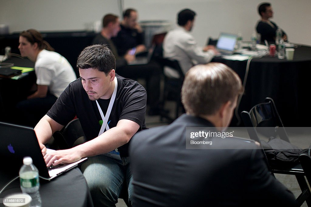 Eugene Mandel from CatchFree Inc., left, works on a laptop computer at the TechCrunch Disrupt NYC 2011 conference in New York, U.S., on Tuesday, May 24, 2011. The summit brings together leaders from various tech fields to discuss how the internet is disrupting industry after industry, from media and social commerce to payments and transportation. Photographer: Guy Calaf/Bloomberg via Getty Images