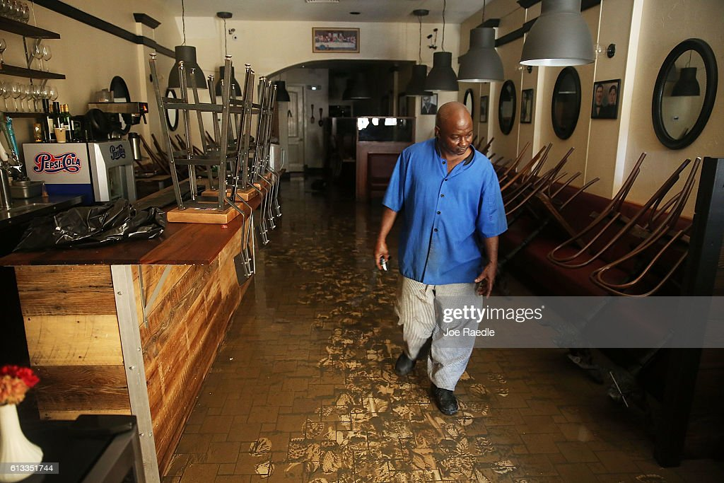 Eugene Scott walks through the muck on the floor of Athena Restaurant after it was flooded by water as Hurricane Matthew passed through the area on...