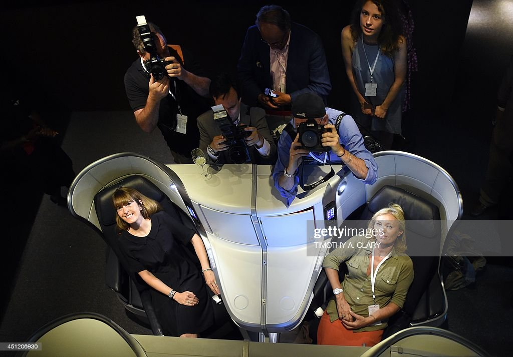 Eugenie Audebert from Air France (L) and a journalist try out the new business class seating at the new Air France Exhibition called 'Air France,france is in the Air' in New York June 25, 2014. Air France held a news conference unveiling the new Upscale Experience on the Paris-New York route with the new economy, premium economy and business cabins on board Boeing 777's. AFP PHOTO / Timothy A. CLARY