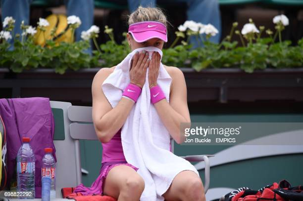 Eugenie Bouchard wipes her face with a towel as she sits dejected during her 1st round women's singles match against Kristina Mladenovic on day three...