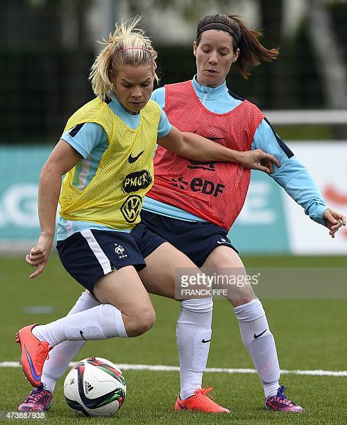 Eugenie Le Sommer of the French national womens football team vies with teammate Clarisse Le Bihan during a training session in...