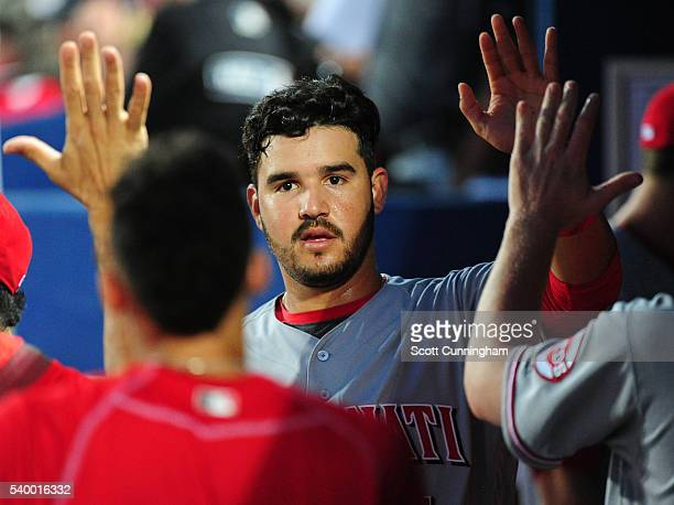 Eugenio Suarez of the Cincinnati Reds is congratulated by teammates after scoring a sixth inning run against the Atlanta Braves at Turner Field on...