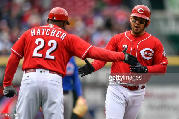 Eugenio Suarez of the Cincinnati Reds is congratulated by Third Base Coach Billy Hatcher of the Cincinnati Reds after hitting a home run against the...