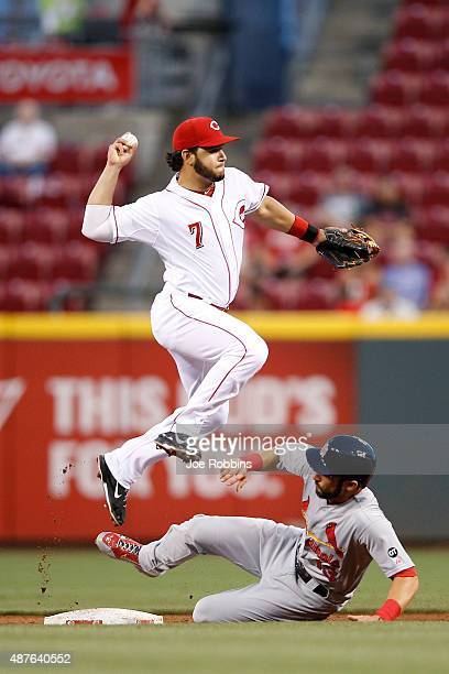 Eugenio Suarez of the Cincinnati Reds turns a double play over Matt Carpenter of the St Louis Cardinals in the third inning at Great American Ball...