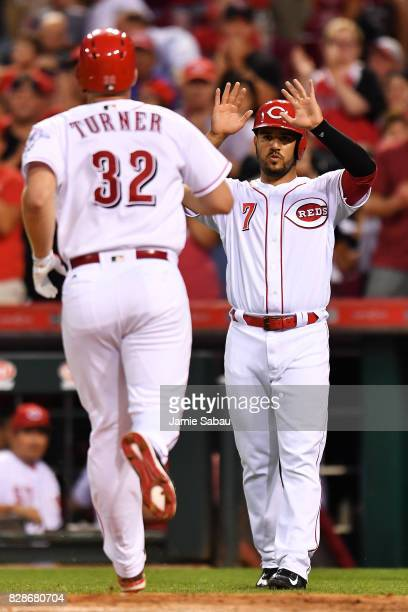 Eugenio Suarez of the Cincinnati Reds waits to congratulate Stuart Turner of the Cincinnati Reds at home plate after Turner hit a tworun home run in...