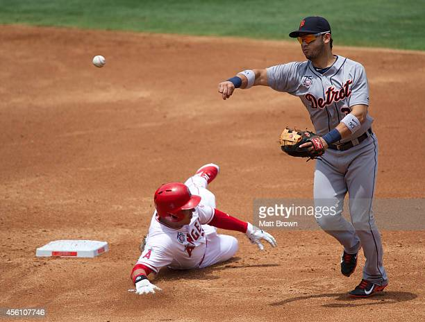 Eugenio Suarez of the Detroit Tigers throws the ball to first base as Efren Navarro of the Los Angeles Angels of Anaheim slides into second base...