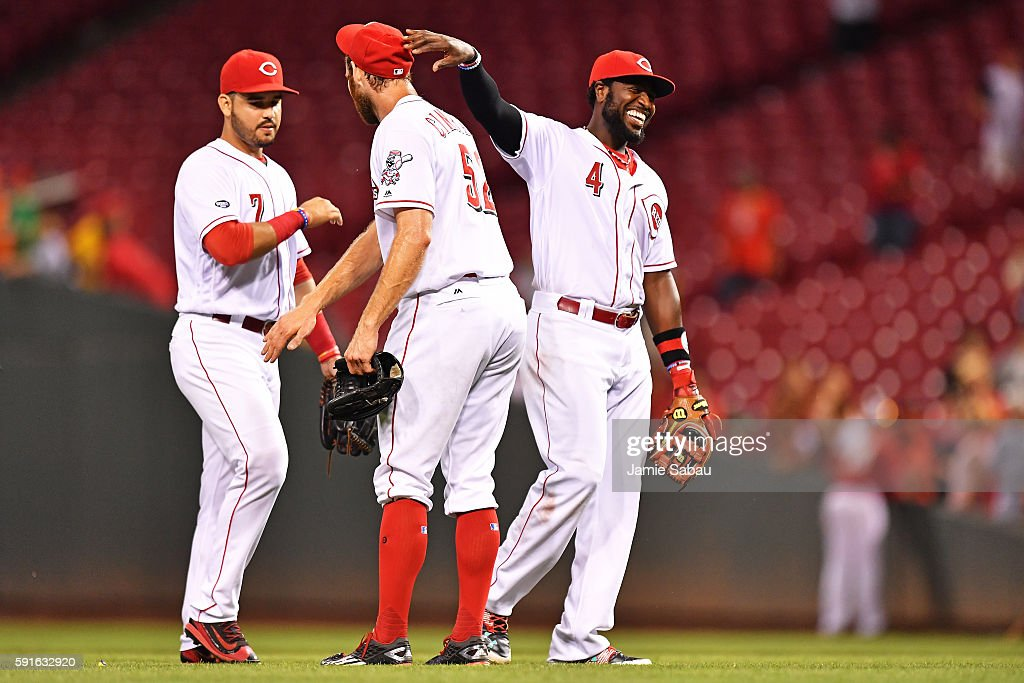 Eugenio Suarez Tony Cingrani and Brandon Phillips all of the Cincinnati Reds celebrate on the field after defeating the Miami Marlins 32 at Great...