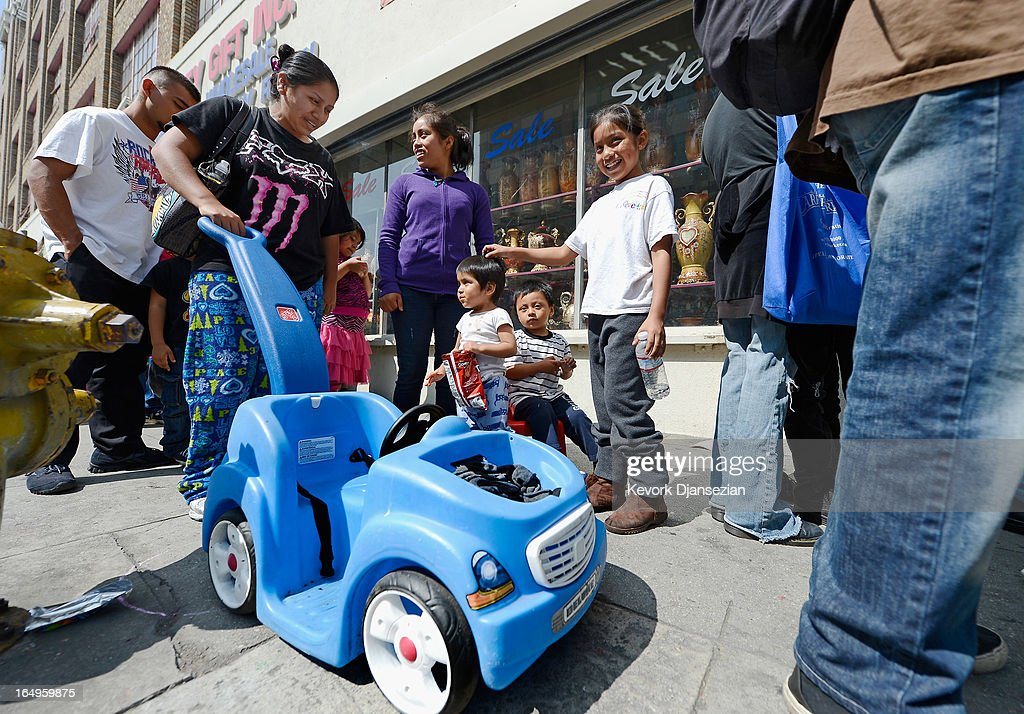 Eulla Gonzalez (L) and family members Quetzal Gonzalez (R), 9, Karla Hernandez (C), 16, Fidel Hernandez, 1, and Eduardo Matul, 4, wait in line for dinner on Good Friday during the Skid Row Easter event at the Los Angeles Mission on March 29, 2013 in Los Angeles, California. Volunteers, celebrities and nurses distributed more than 1000 Easter baskets to children and provided 3,500 hot meals, 2,000 pairs of shoes and and podiatric care to the homeless of Skid Row.