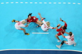 Eun Bi Lee of Korea is brought down by Rikke Skov of Denmark during the Women's Handball Preliminaries Group B Match 8 between Korea and Denmark on...