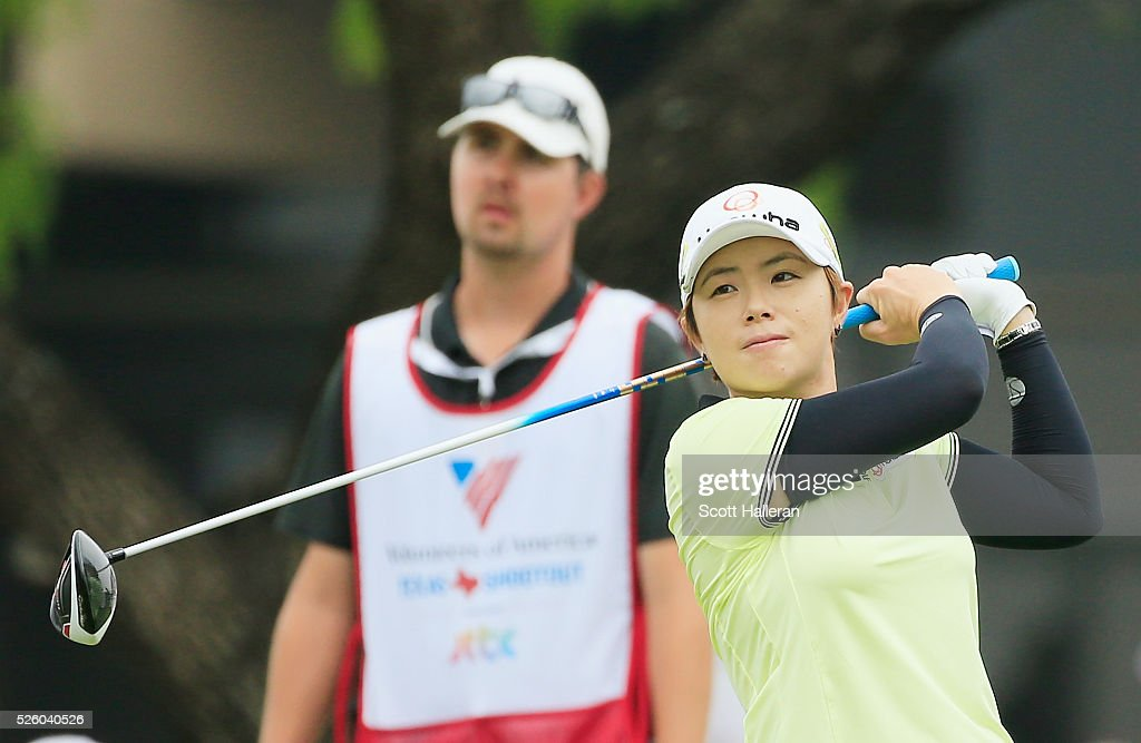 Eun-Hee Ji of South Korea watches her tee shot on the first hole as her caddie looks on during the second round of the Volunteers of America Texas Shootout at Las Colinas Country Club on April 29, 2016 in Irving, Texas.