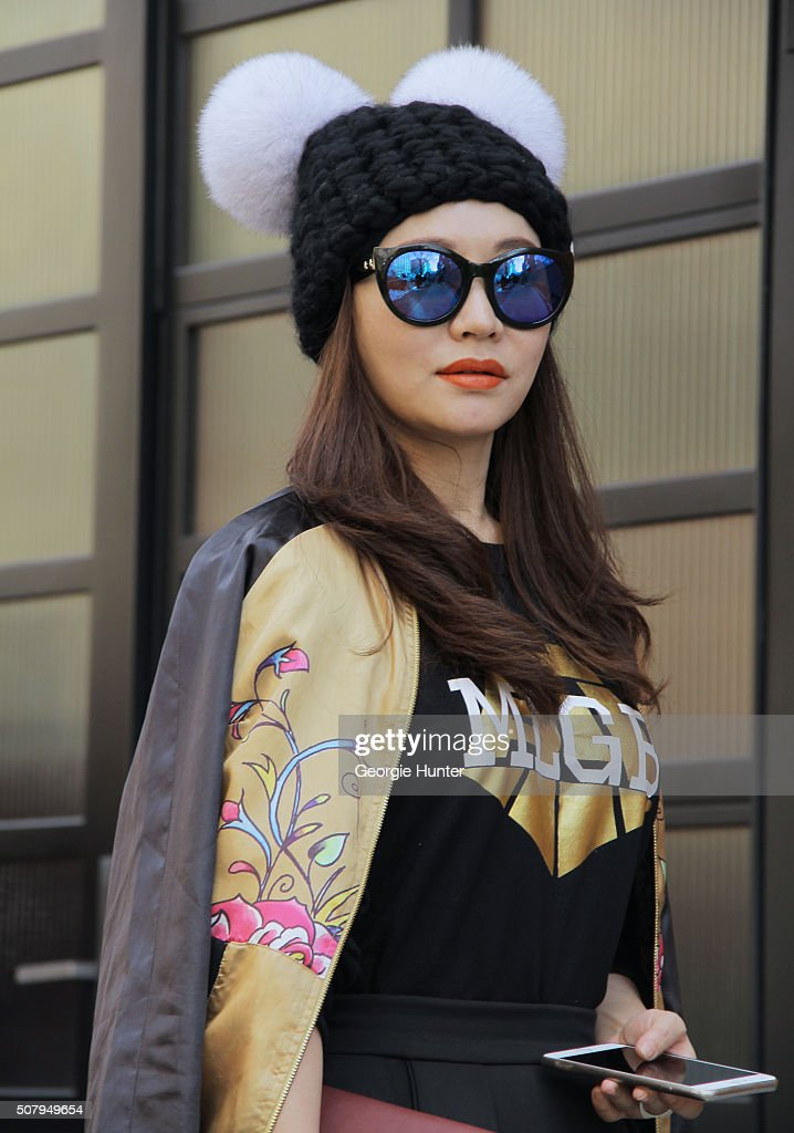 Eunice Zhang seen at Industria Superstudios wearing black high waisted pleated skirt gold Ed Hardy silk embroidered bomber jacket Jiang sweater...