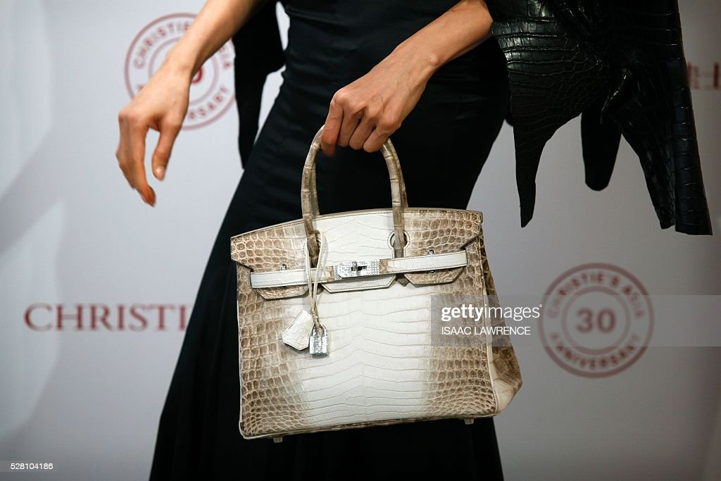 Eunis Chan models a Matte White Himalaya Niloticus Crocodile Diamond Birkin with 18K gold and diamond hardware -- one of the most valuable handbags in the world -- during a preview at Christies in Hong Kong on May 4, 2016. / AFP / ISAAC