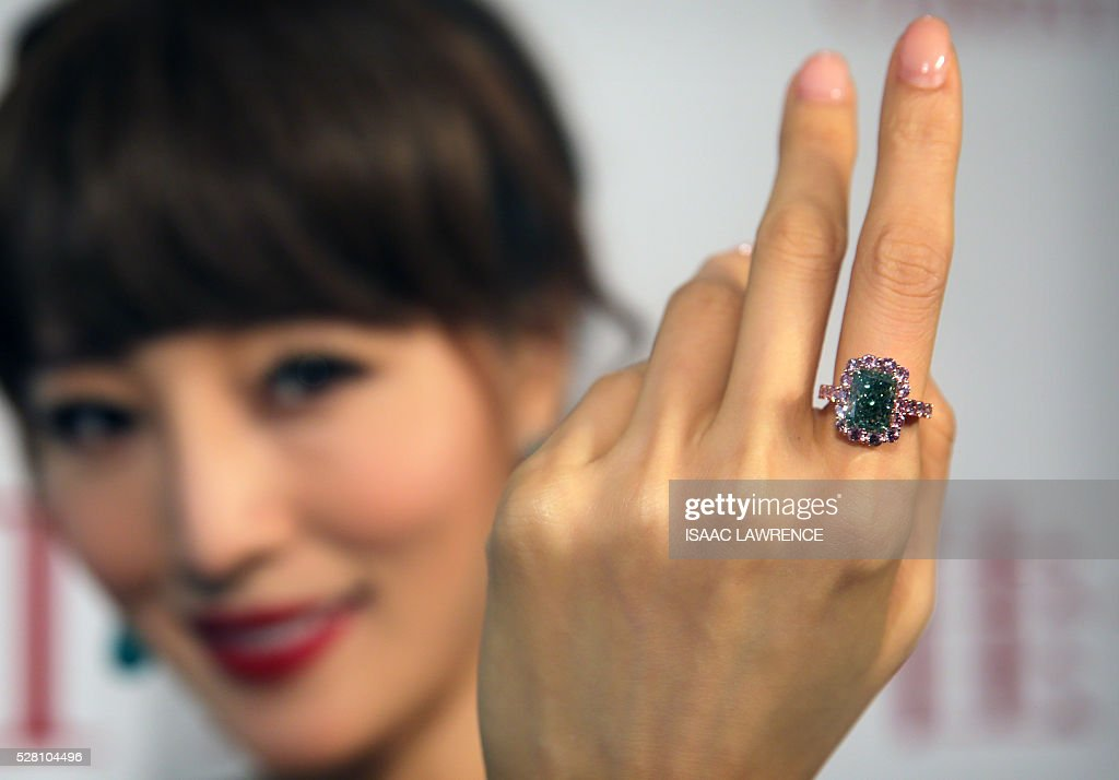 Eunis Chan models the 5.03 carat Aurora Green diamond -- the worlds largest fancy vivid green diamond in the world, when auctioned is expected to fetch between 16 million USD and 20 million USD -- during a preview at Christies in Hong Kong on May 4, 2016. / AFP / ISAAC