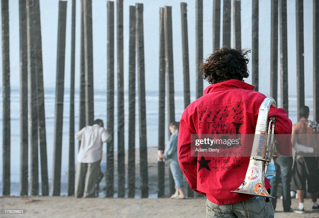 A euphonium player passes in front of a photo of the United States-Mexico border in Tijuana, Mexico, as it hangs as part of the 'Wall on Wall' exhibition at the East Side Gallery section of the former Berlin Wall on July 10, 2013 in Berlin, Germany. A series of photos shot since 2006 by photographer Kai Wiedenhoefer hanging on the Western, river Spree side of the Wall features large pictures of separation barriers in Baghdad, Korea, Cyprus, Mexico, Morocco, Israel, Belfast, and in the former East Germany itself. The opposite side of the stretch of the original Wall is known as East Side Gallery, a memorial to peace and freedom covered in murals questioning the legacy of the original Wall, and the subject of several demonstrations earlier in March this year when sections of it were threatened with removal to make way for a construction site for luxury apartment buildings, discussion of which is still ongoing with a decision expected to be reached in early August.