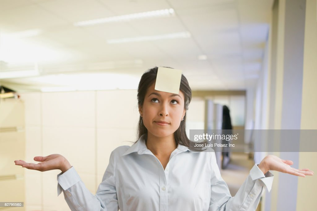 Eurasian businesswoman gesturing with sticky note on forehead : Stock Photo
