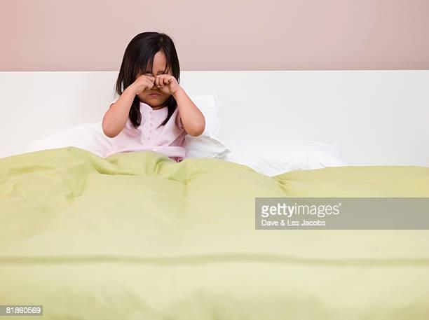 Eurasian girl rubbing eyes