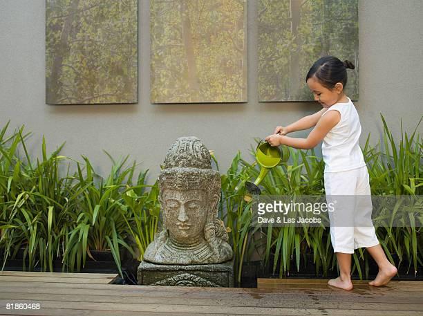 Eurasian girl watering plants