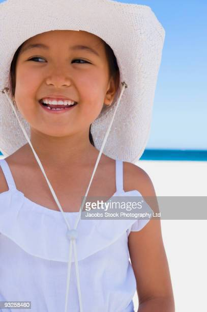 Eurasian girl wearing sun hat on beach