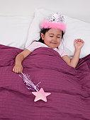 Eurasian girl wearing tiara in bed