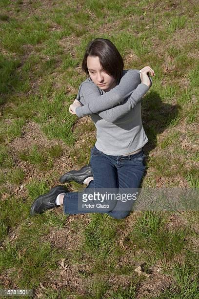 Eurasian teenage girl at a park removing her shirt