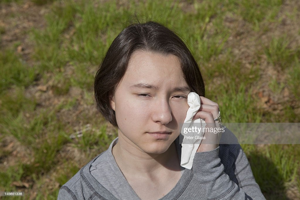 Eurasian teenage girl wiping face with a tissue. : Stock Photo