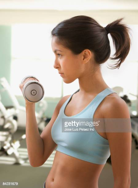 Eurasian woman lifting dumbbells in health club