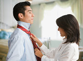 Eurasian woman tying Korean man's tie