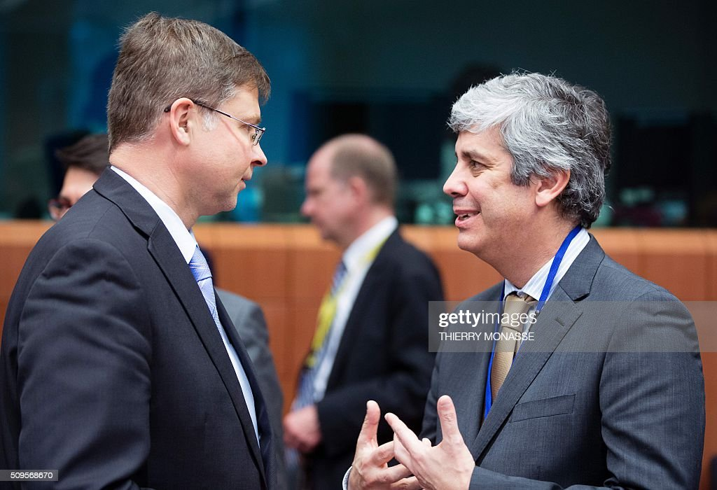 EU Euro and Social Dialogue Commissioner Valdis Dombrovskis (L) talks with Portuguese Finance Minister Mário Centeno (R) prior to a meeting of Eurogroup ministers at the European Council headquarters in Brussels on February 11, 2016. / AFP / THIERRY MONASSE