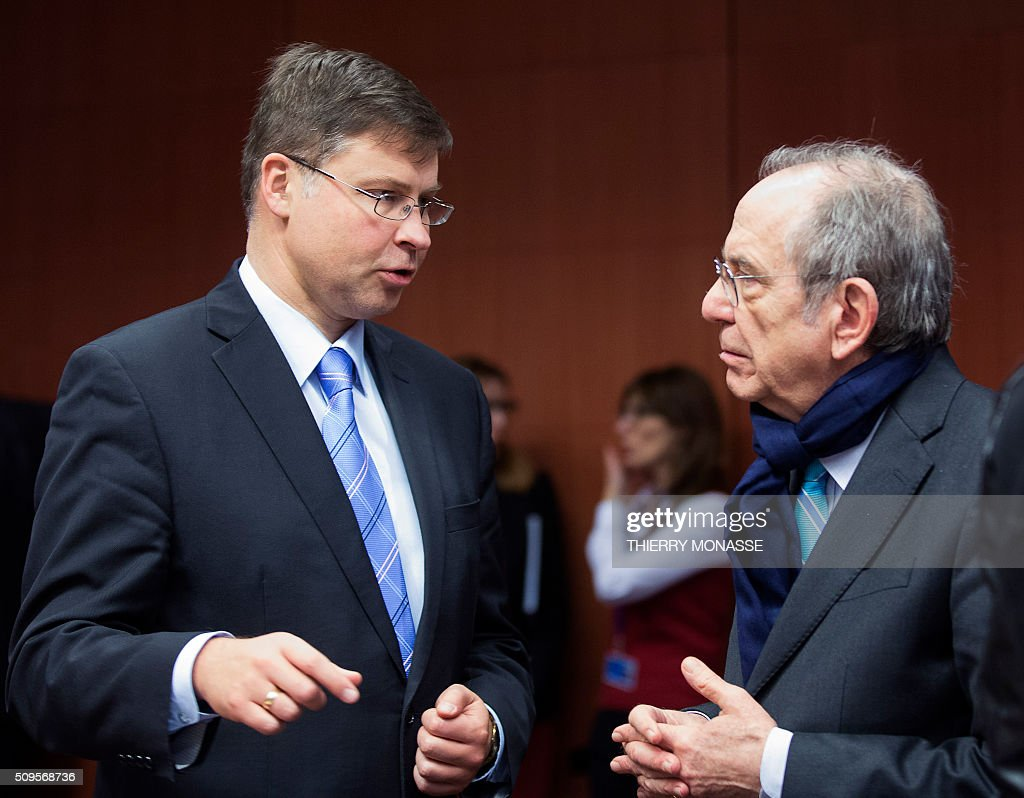 EU Euro and Social Dialogue Commissioner Valdis Dombrovskis (L) talks with Italian Economy and Finance Minister Pier Carlo Padoan (R) prior to a meeting of Eurogroup ministers at the European Council headquarters in Brussels on February 11, 2016. / AFP / THIERRY MONASSE