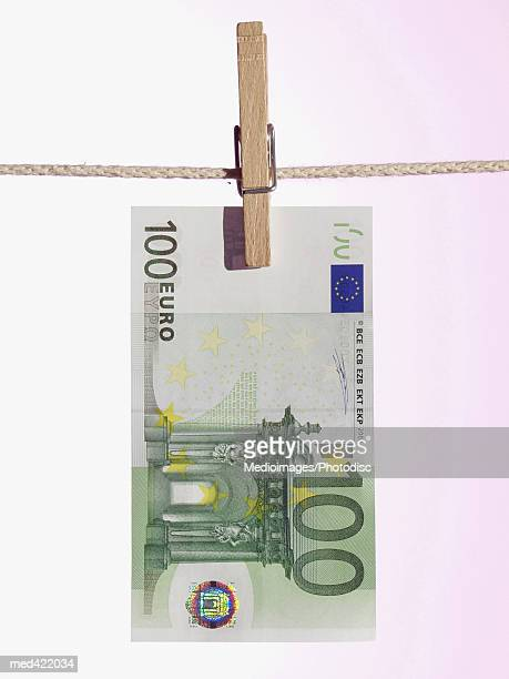 A Euro bank note hung on a clothes line with a clothes peg