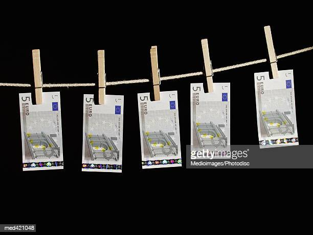 Euro bank notes hung on a clothes line with clothes pegs