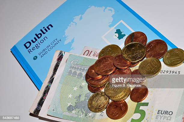 Euro banknotes and coins on a info book about Dublin