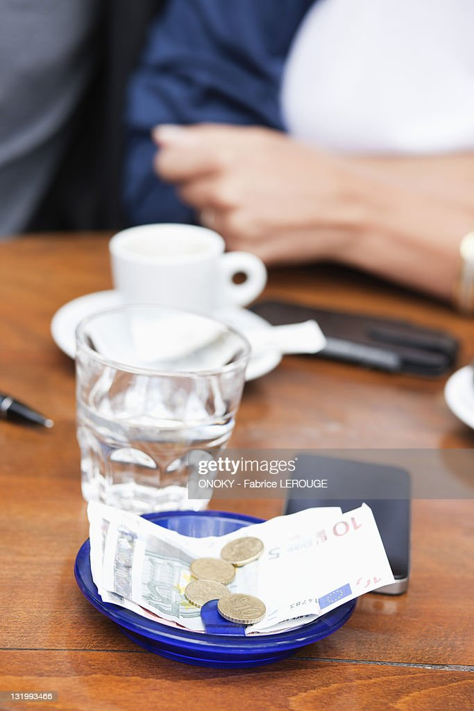 Euro banknotes and coins with bill on a table in a restaurant, Paris, Ile-de-France, France : Stock Photo