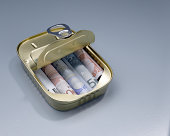 Euro banknotes in sardine can with open lid, studio shot