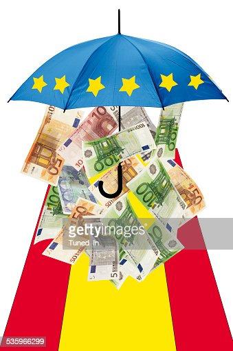 Euro banknotes under umbrella with spanish flag : Stock Photo