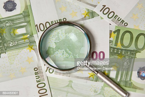100 Euro banknotes with magnifying glass