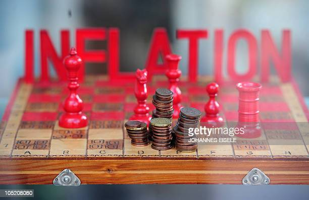 Euro cents are seen on a chessboard and the word 'inflation' as a part of a advertisement on October 12 2010 in Berlin AFP PHOTO / JOHANNES EISELE