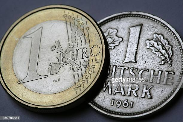 Euro coin and a 1 German mark next to each other
